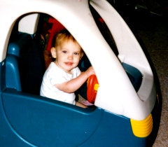 Hannah age 18 months driving in a toy car