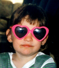 Hannah age 3 with big heart shaped sun glasses